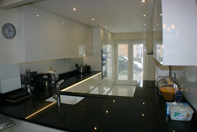 Handle less white gloss porcelain kitchen installation for Eye level oven kitchen designs